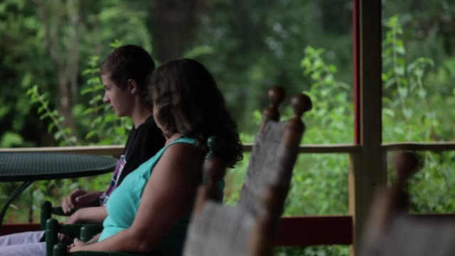 Teenage boy and mature woman in rocking chairs on an outdoor porch