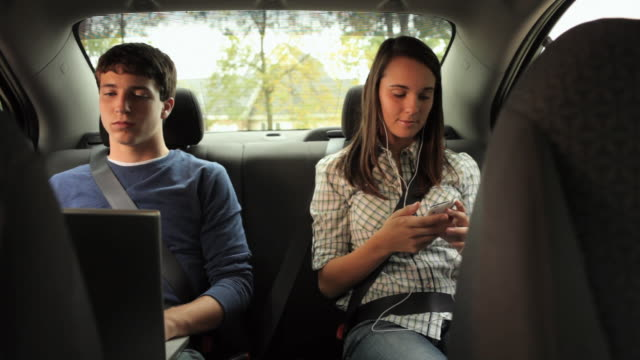 ms teenage boy (16-17) and teenage girl (16-17) listening to mp3 player in back seat of car / neenah, wisconsin, usa   - neenah stock videos & royalty-free footage