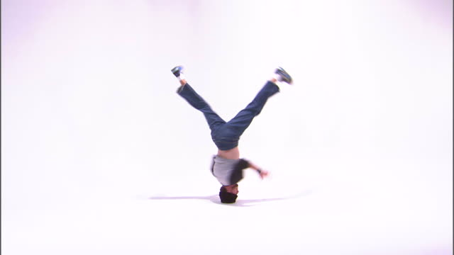 WS Teenage boy (14-15) breakdancing, performing headstand, against white background / Orem, Utah, USA