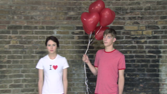 teenage boy bringing heart shaped balloons to girlfriend - 渡す点の映像素材/bロール