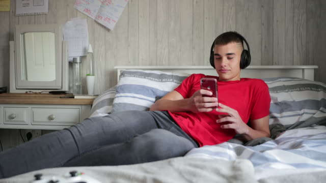 vídeos de stock e filmes b-roll de teenage boy busy on phone - independência