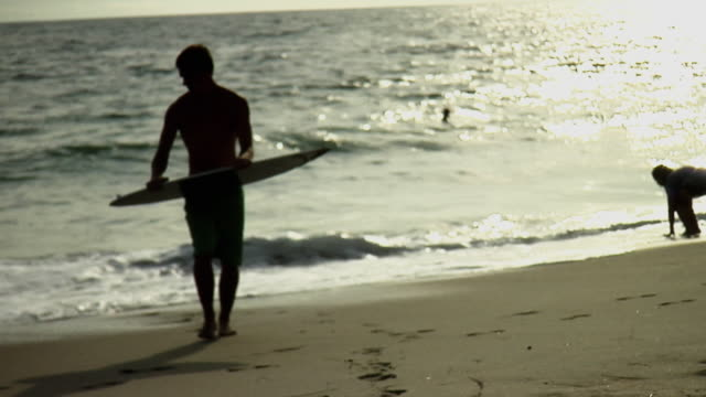 ws teenage boy (16-17) carrying skim board on beach / laguna beach, california, usa - skimboard stock videos and b-roll footage
