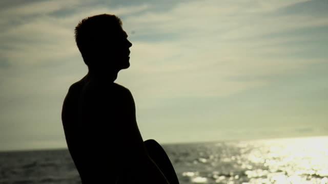 CU TD MS Teenage boy carrying surfboard walking towards sea, Laguna Beach, California USA