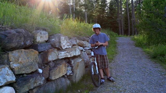 teenage boy checks phone message, hops on bike - phone message stock videos & royalty-free footage