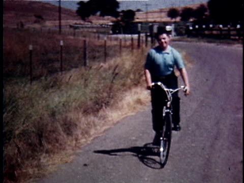 WS TS Teenage boy cheerfully riding bicycle along country road / USA