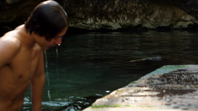 r/f teenage boy climbing out of water after swimming in cenote while on vacation - un ragazzo adolescente video stock e b–roll