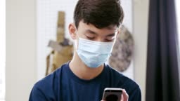 A teenage boy communicates with friends during coronavirus pandemic