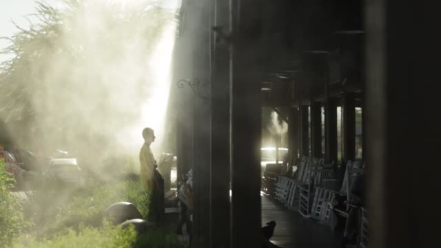 Teenage boy cooling off under misting apparatus