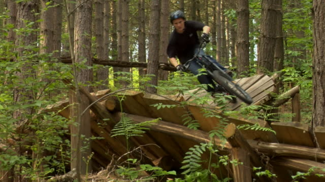 ws pan teenage boy cycling on curved wooden ramp in bedgebury forest / kent, england, uk  - see other clips from this shoot 1036 stock videos and b-roll footage