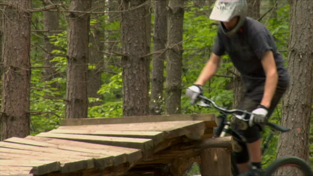 slo mo la cu teenage boy cycling on ramp in bedgebury forest / kent, england, uk - one teenage boy only stock videos & royalty-free footage