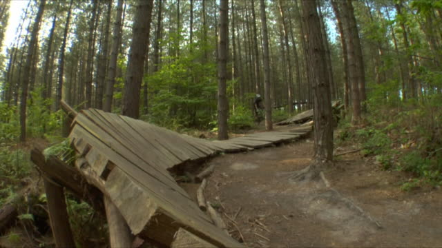 SLO MO LA WS Teenage boy cycling on wooden ramp in Bedgebury Forest / Kent, England, UK