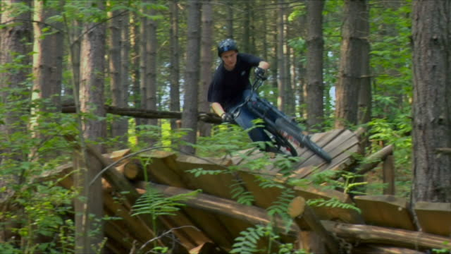 WS PAN Teenage boy cycling on wooden ramp in Bedgebury Forest / Kent, England, UK