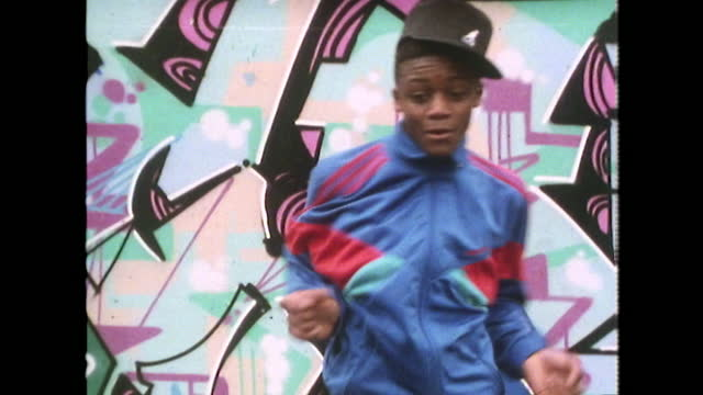 vídeos de stock e filmes b-roll de teenage boy dances to rap music in front of graffiti; london, 1989 - cultura hip hop