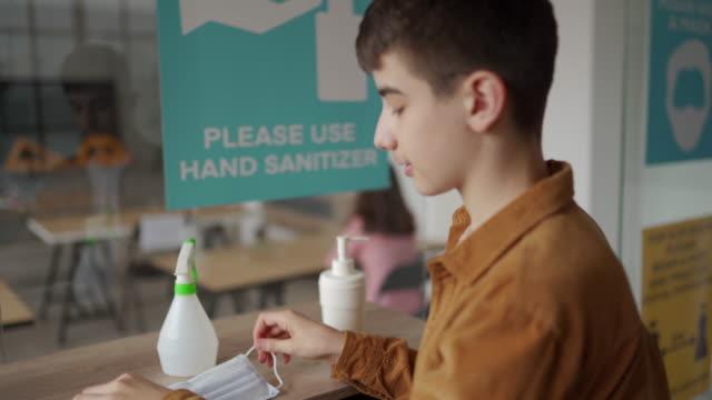 stockvideo's en b-roll-footage met tiener die handen met handontsmettingsmiddel ontsmet en het zetten op beschermend gezichtsmasker bij klaslokaal deinseert - heropening