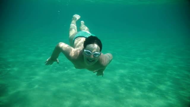 Teenage boy diving in the ocean.halo greeting