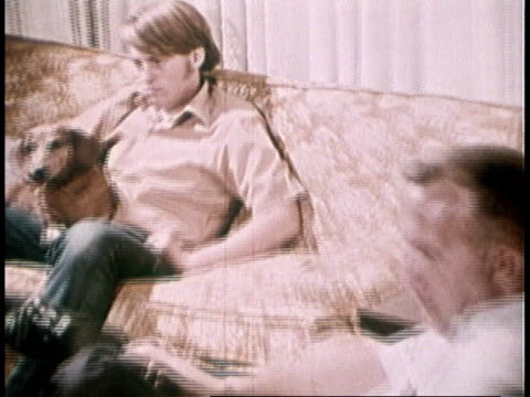 1973 montage teenage boy, dog, and dad sitting on couch watching television, dad asking about election / united states - watching tv stock videos & royalty-free footage