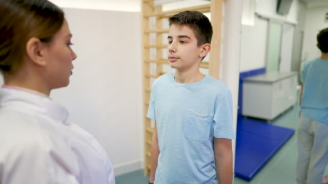teenage boy doing therapeutic exercises with his doctor in the rehabilitation center - rehabilitation center stock videos & royalty-free footage