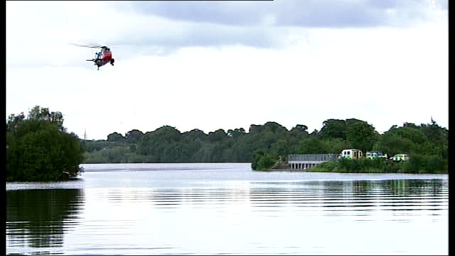 teenage boy drowns whilst swimming in lanarkshire loch; scotland: lanarkshire: banton loch: ext search helicopter hovering over loch police divers in... - searching点の映像素材/bロール