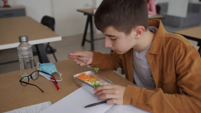 teenage boy eating healthy food during lunch break at classroom - lunch break stock videos & royalty-free footage