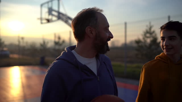 teenage boy enjoying together time with his father on basketball court - son stock videos & royalty-free footage