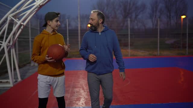 teenager genießt zusammen zeit mit seinem vater auf dem basketballplatz - son stock-videos und b-roll-filmmaterial