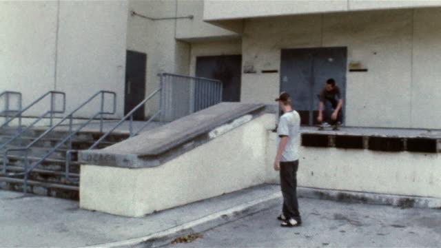 teenage boy filming skater ollieing onto ramp, sliding along lip and landing on sidewalk - trucker cap stock videos & royalty-free footage