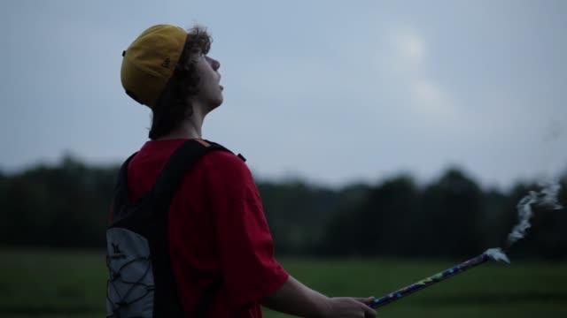 teenage boy firing off roman candle at dusk - un ragazzo adolescente video stock e b–roll