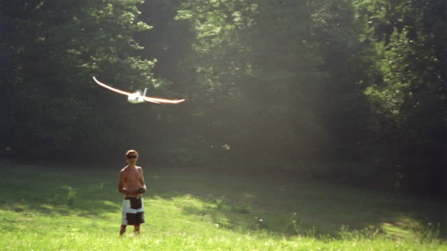 teenage boy flying remote control aircraft in field / saint-ferme, france - one teenage boy only stock videos and b-roll footage