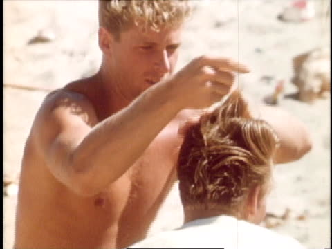 teenage boy getting his hair styled on beach with ducktail hairdo - malibu stock videos & royalty-free footage