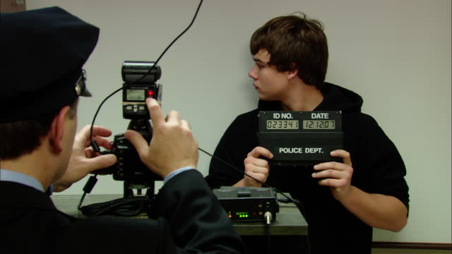 stockvideo's en b-roll-footage met ms teenage boy getting mugs hot taken at police station/ new jersey - schulden