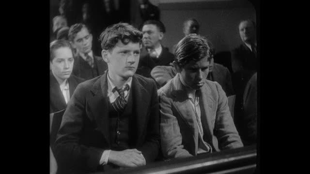 1932 a teenage boy has a false sense of security at juvenile court - gerichtssaal stock-videos und b-roll-filmmaterial