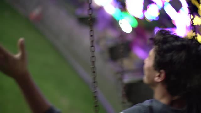 rv teenage boy having fun on a ride at a carnival. - volksfest stock-videos und b-roll-filmmaterial
