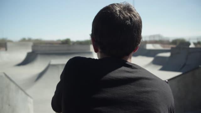 vídeos y material grabado en eventos de stock de teenage boy heads down ramp on bmx bike in a skate park - un solo adolescente