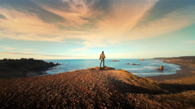 teenage boy hiking trail on pacific ocean at sunset, oregon - avventura video stock e b–roll