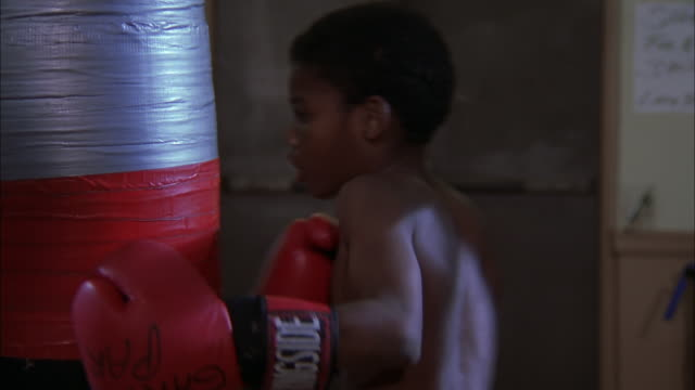 Teenage boy hitting punch bag at boxing club, Illinois, Chicago Available in HD.