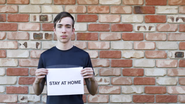 teenage boy holding stay at home sign - pleading stock videos & royalty-free footage