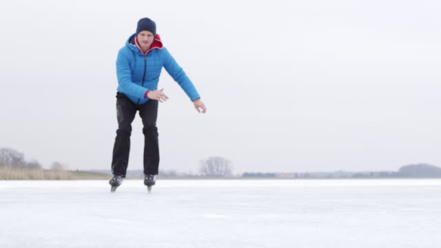 4K Teenage boy ice skating and falling on frozen lake, slow motion