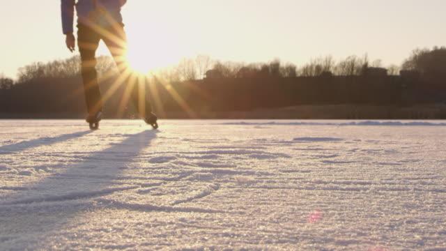 4K Teenage boy ice skating and sliding on sunny idyllic frozen lake, slow motion
