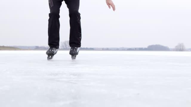 vídeos de stock e filmes b-roll de 4k teenage boy ice skating on frozen lake, slow motion - patinagem no gelo