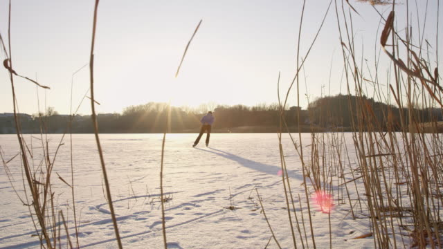 4k teenage boy ice skating on sunny, idyllic frozen lake, slow motion - ice skating stock videos & royalty-free footage