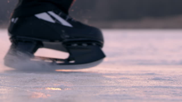 4k teenage boy ice skating, sliding on frozen lake, slow motion - ice skating stock videos & royalty-free footage