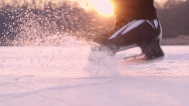 4K Teenage boy ice skating, spinning on frozen lake, slow motion