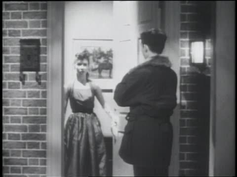 b/w 1953 rear view teenage boy in coat ringing doorbell of house / girl answers + lets him in - teenagerpaar stock-videos und b-roll-filmmaterial