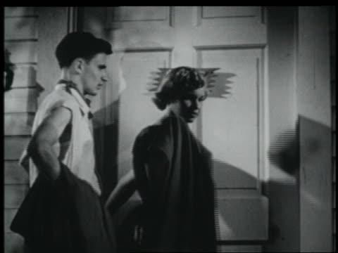 vídeos y material grabado en eventos de stock de b/w 1951 teenage boy in greaser wear picking up girl at house for date + helping her put on her coat - 1951