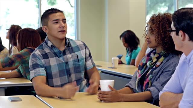 vidéos et rushes de jeune garçon au lycée expliquer quelque chose à groupe d'étude - jeunes filles