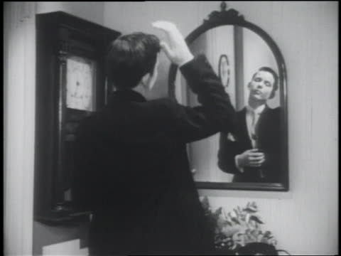 b/w 1953 rear view teenage boy in suit primping in front of mirror / puts on coat and exits - mirror stock videos & royalty-free footage