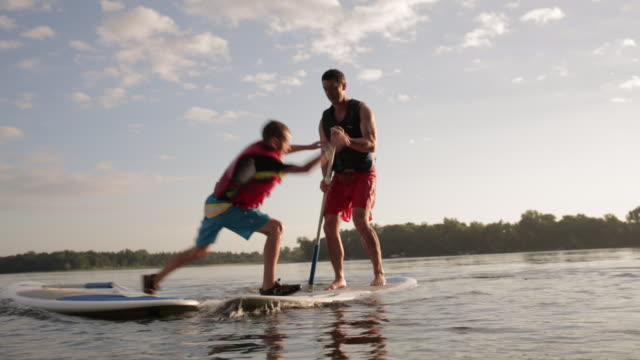 stockvideo's en b-roll-footage met teenage boy jumping on father's paddleboard while making him fall in lake - tienerjongens