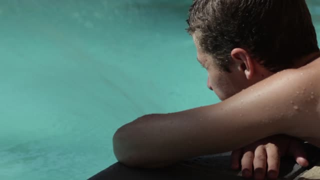 cu of teenage boy laying poolside - one teenage boy only stock videos and b-roll footage