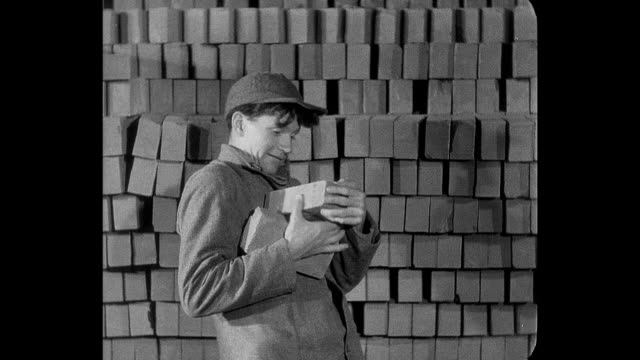 stockvideo's en b-roll-footage met 1932 a teenage boy learns the reality of reform school while stacking bricks - baksteen