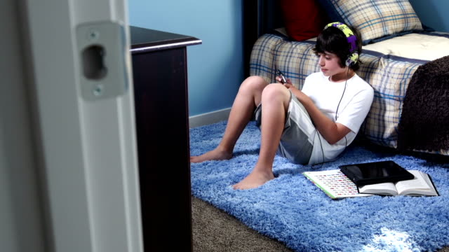 teenage boy listens to music on mp3 player - modern bedroom stock videos & royalty-free footage